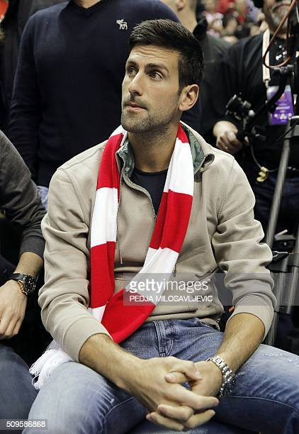 Serbian tennis player Novak Djokovic weares Crvena Zvezda scarf as he attends the Euroleague Top 16 basketball match between Crvena Zvezda Telekom...