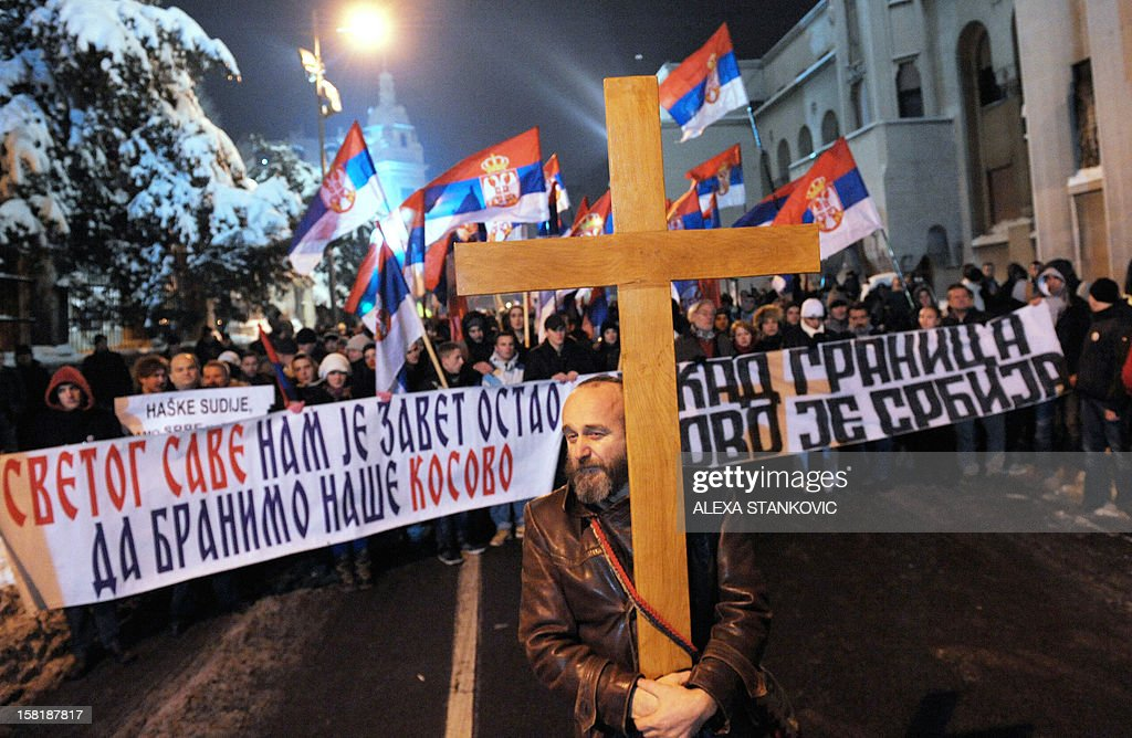 A Serbian ultra-nationalist carries a wooden cross in Belgrade on December 10, 2012, as he takes part in a protest against the openings of jointly operated crossing points between Serbia and Kosovo. The first two disputed crossings on the flashpoint border between Serbia and Kosovo opened on December 10 following a EU-mediated deal on joint border management between Pristina and Belgrade which has still been rejecting unilaterally declared independence of its former province.