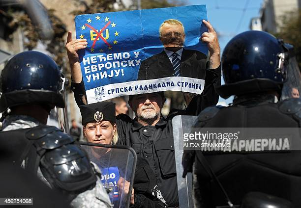 Serbian ultranationalists hold a banner showing Serbian Radical Party leader Vojislav Seselj reading 'We don't want to join the EU' during a protest...