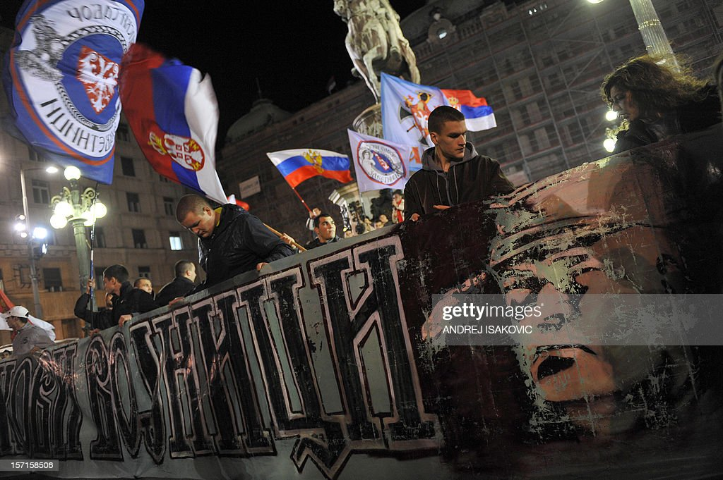 Serbian ultra-nationalists wave flags of Serbia and hold a banner bearing a picture of former Bosnian Serb army chief Ratko Mladic during a rally to protest after a UN court cleared Kosovo's former prime minister Ramush Haradinaj of war crimes committed during the 1998-1999 conflict, in Belgrade on November 29, 2012. A UN war crimes court on November 29, cleared Haradinaj of murder and torture during the 1990s war of independence, enraging Belgrade with the second such acquittal in two weeks. The Hague-based International Criminal Tribunal for the former Yugoslavia (ICTY) cleared the former military commander and two of his former guerrilla comrades after a case that lasted seven years. AFP PHOTO / ANDREJ ISAKOVIC