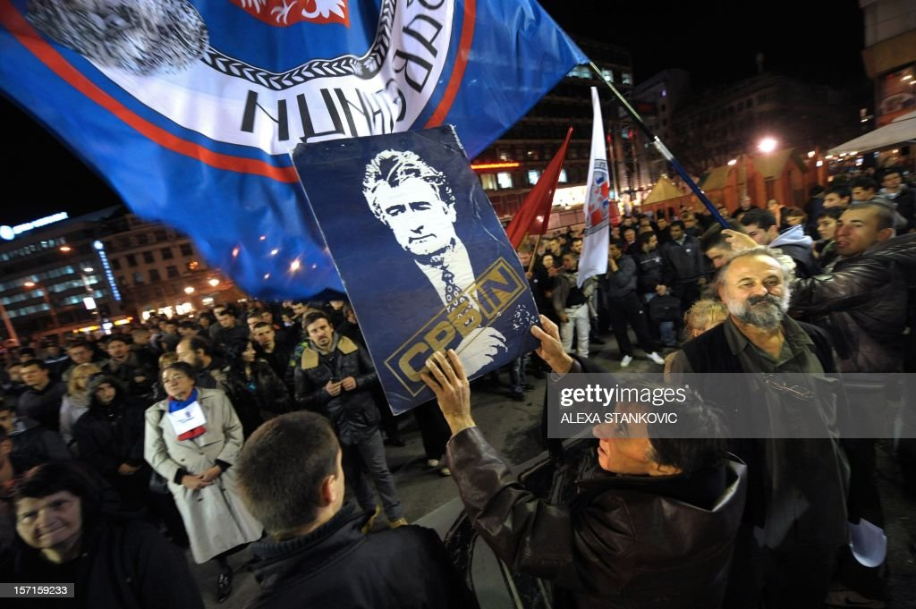 Serbian ultra-nationalists wave flags of Serbia and hold a banner bearing a picture of former Bosnian Serb leader Radovan Karadzic during a rally to protest after a UN court cleared Kosovo's former prime minister Ramush Haradinaj of war crimes committed during the 1998-1999 conflict, in Belgrade on November 29, 2012. A UN war crimes court on November 29, cleared Haradinaj of murder and torture during the 1990s war of independence, enraging Belgrade with the second such acquittal in two weeks. The Hague-based International Criminal Tribunal for the former Yugoslavia (ICTY) cleared the former military commander and two of his former guerrilla comrades after a case that lasted seven years.
