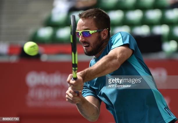 Serbian Viktor Troicki returns a shot to Canada's Milos Raonic during their men's singles first round match at the Japan Open tennis tournament in...