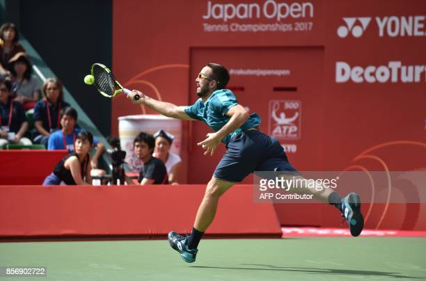 Serbian Viktor Troicki tries to return a shot to Canada's Milos Raonic during their men's singles first round match at the Japan Open tennis...