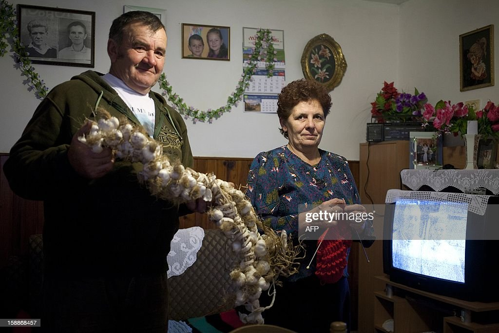 Serbian villager holds a garlic braid, used as vampire repellant, while his wife knits on December 3, 2012 in the western Serbian village of Zarozje, some 140km from Belgrade. The leering visage of a gap-toothed man with blood dripping down his stubbly chin is an unusual image to sell a town, but in the tiny Serbian hamlet of Zarozje, locals are hoping a resurrected vampire legend will let them bleed a little cash from passing visitors.