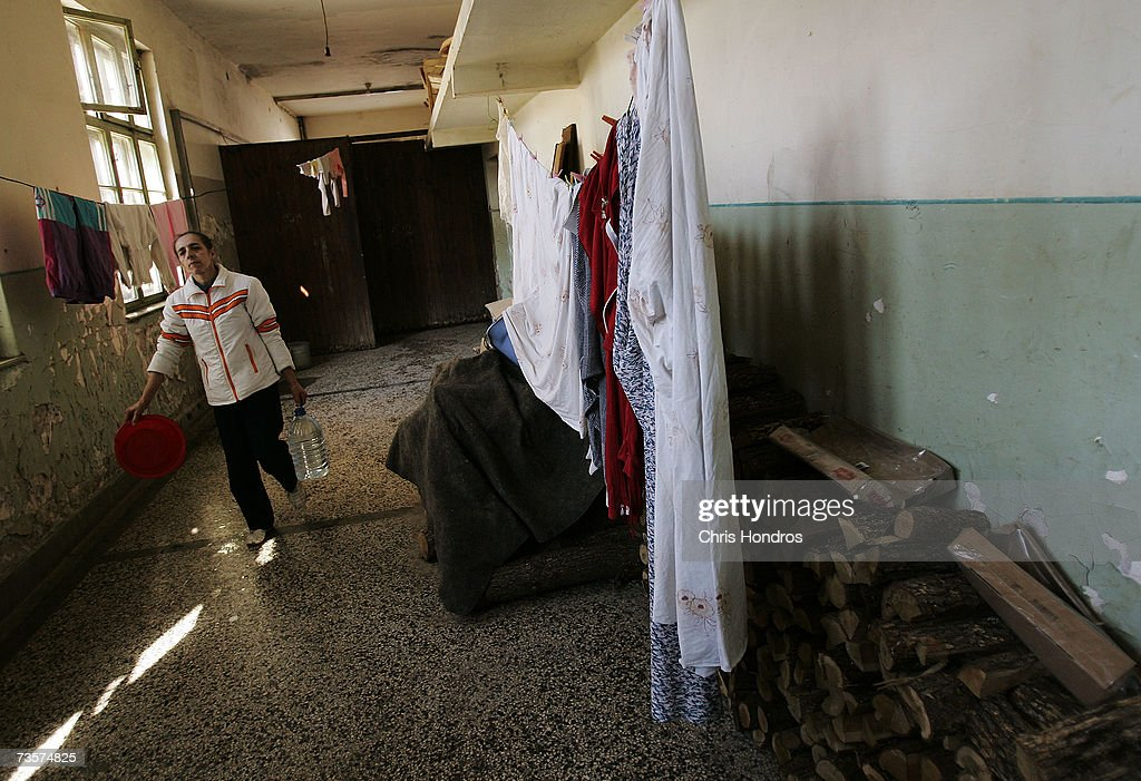 A Serbian woman carries water past laundry in the hallway of an abandoned school being used by Serbian refugees who fled from villages in Albanian-dominated Kosovo March 14, 2007 in Mitrovica, Kosovo. Mitrovica, before 1999 a town where Serbs and ethnic Albanians lived side-by-side, now is Kosovo's most glaring symbol of separation, as the two populations quickly separated themselves after the fall of the Serbian government in Kosovo and occupied opposite banks of the Ibar river. Serbs fleeing from ethnic Albanian reprisal attacks fled to Serbian northern Mitrovica in 1999, settling down in this abandoned school, where they remain today.