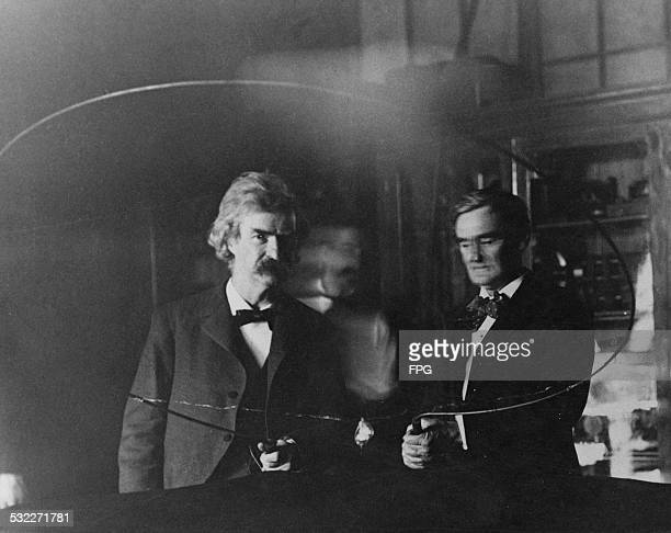 SerbianAmerican inventor and engineer Nikola Tesla performs an electrical experiment for writer Samuel Langhorne Clemens aka Mark Twain and actor...