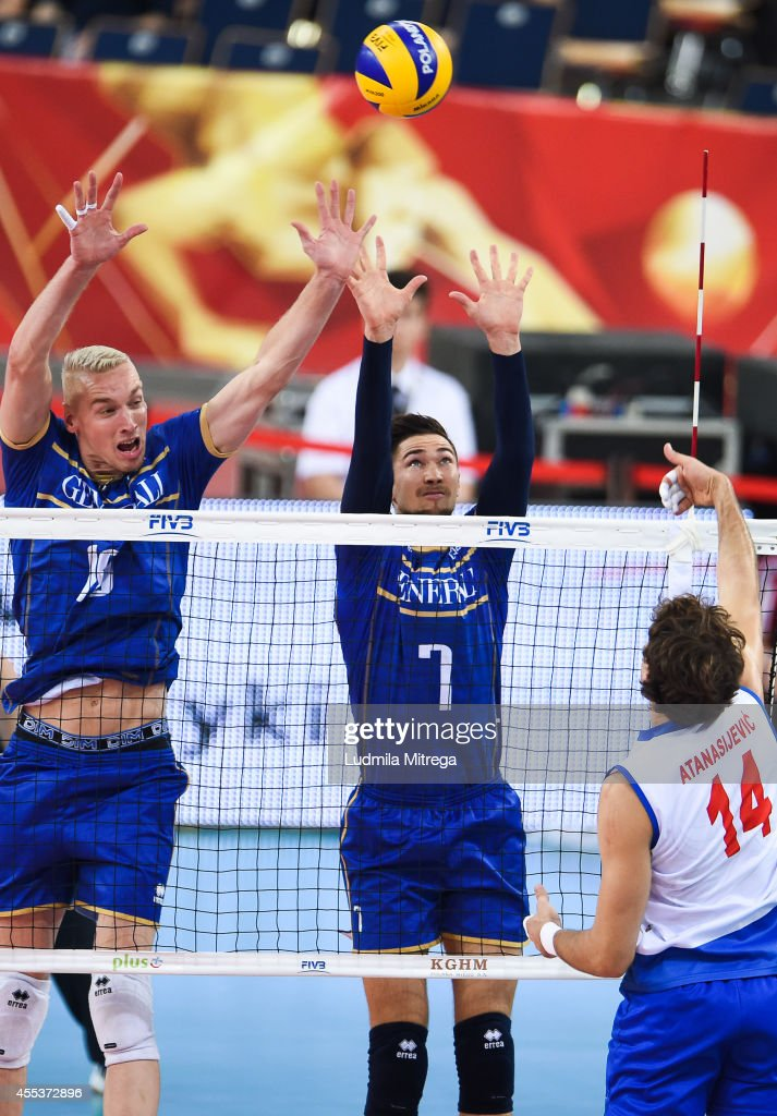 Serbia's Aleksandar Atanasijevic (right) attacks against France's Kevin Le Roux (left) and Kevin Tillie during the FIVB World Championships match between Serbia and France on September 13, 2014 in Lodz, Poland.