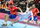 Serbia's Alem Toskic jumps to shoot as he vies with Spain's pivot Gedeon Guardiola Villaplana during the men's preliminaries Group B handball match...