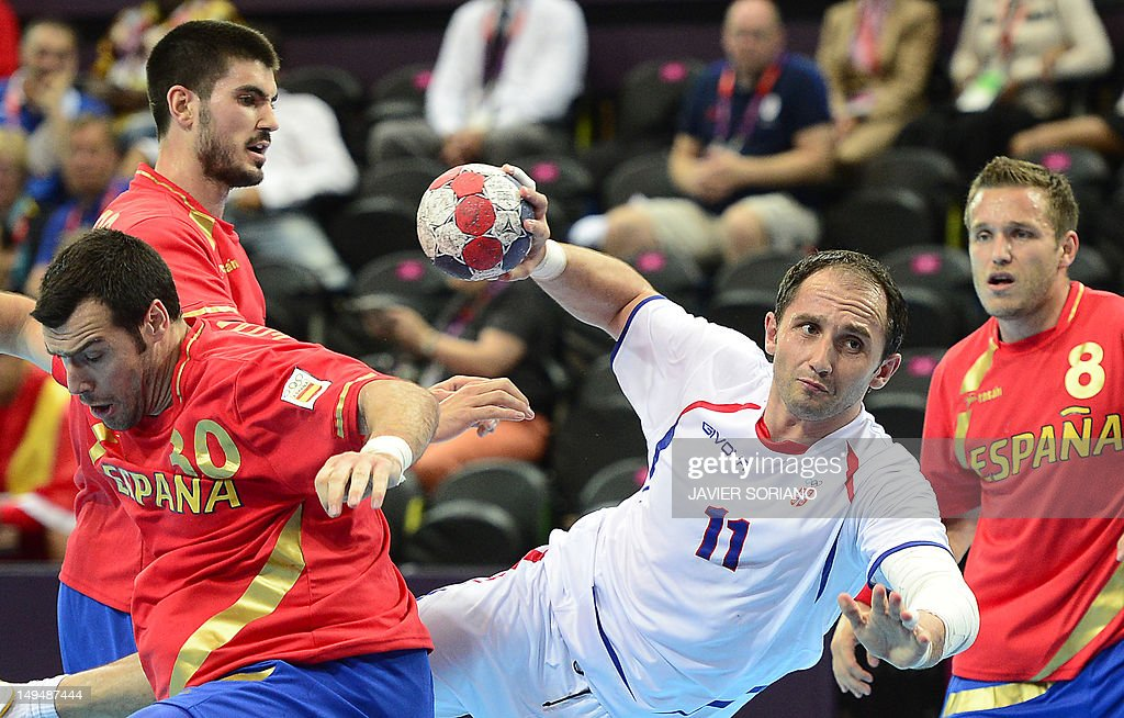 Serbia's Alem Toskic (L) jumps to shoot as he vies with Spain's pivot Gedeon Guardiola Villaplana (L) during the men's preliminaries Group B handball match Spain vs Serbia for the London 2012 Olympics Games on July 29, 2012 at the Copper Box hall in London.