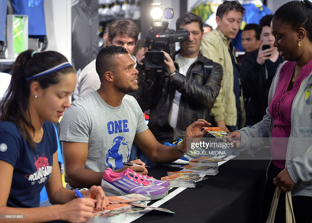 Serbia's Ana Ivanovic (L) and France's Wilfrid Tsonga (C) sign autographs at the Adidas sportswear store in Paris on May 22, 2013, two days ahead of the French Tennis Open tournament. AFP PHOTO MIGUEL MEDINA