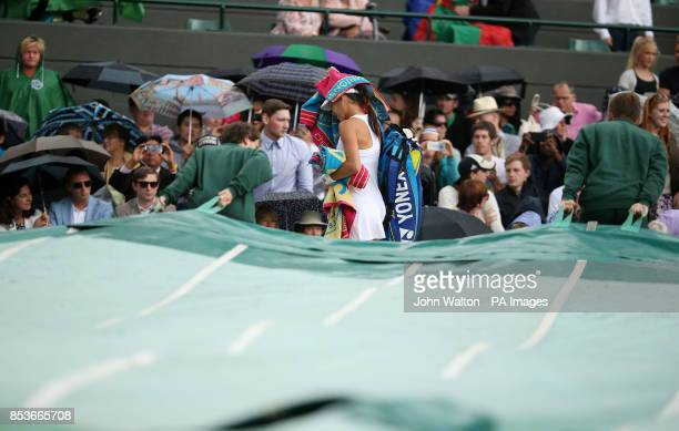 Serbia's Ana Ivanovic leaves the court in her match against Germany's Sabine Lisicki as rain delays play during day eight of the Wimbledon...