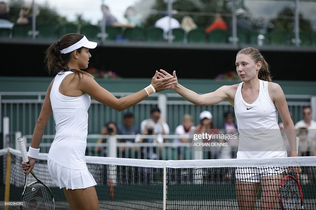 Serbia's Ana Ivanovic (L) shakes hands with Russia's Ekaterina Alexandrova (R) after Alexandrova won their women's singles first round match on the first day of the 2016 Wimbledon Championships at The All England Lawn Tennis Club in Wimbledon, southwest London, on June 27, 2016. / AFP / ADRIAN