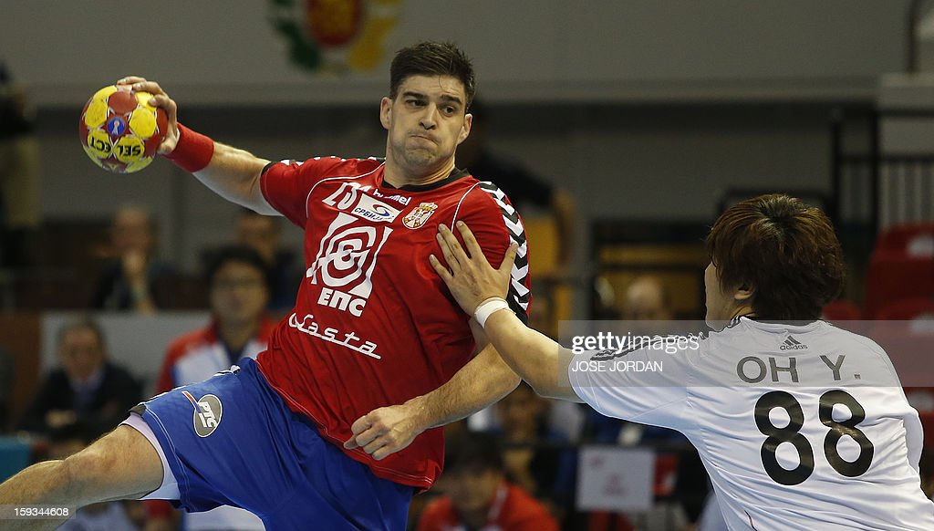 Serbia's back Nenad Vuckovic (L) vies for the balla with Korea's back Yun-Suk Oh during the 23rd Men's Handball World Championships preliminary round Group C match Serbia vs Korea at the Pabellon Principe Felipe in Zaragoza on January 12, 2013.