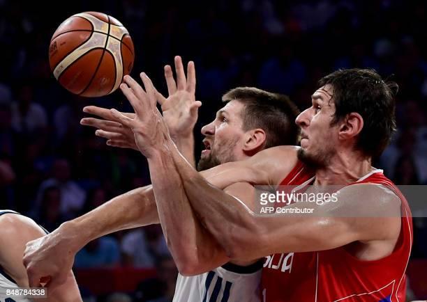 TOPSHOT Serbia's center Boban Marjanovich vies for the ball with Slovenia's center Gasper Vidman and Vlatko Cancar during the FIBA Eurobasket 2017...