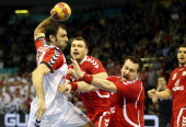 Serbia's centre back Nenad Vuckovic vies with Poland's centre back Michal Kubisztal during the 23rd Men's Handball World Championships preliminary...