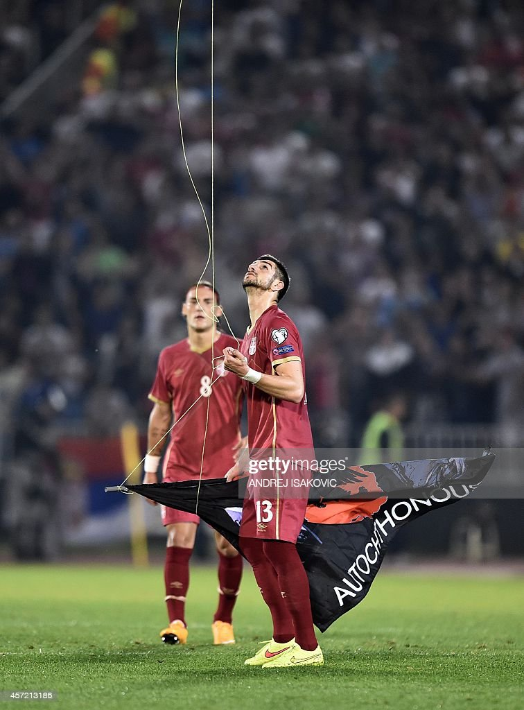 Serbia's defender Stefan Mitrovic grabs a flag with Albanian national symbols flown by a remotely operated drone during the EURO 2016 group I...