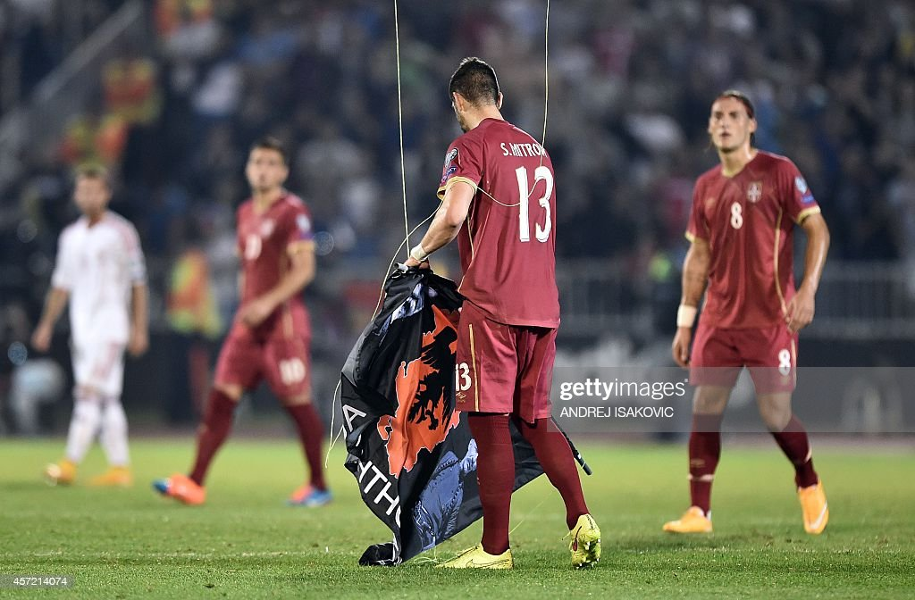 Serbia's defender Stefan Mitrovic grabs a flag with Albanian national symbols from remotely operated drone flown over the pitch during the EURO 2016...