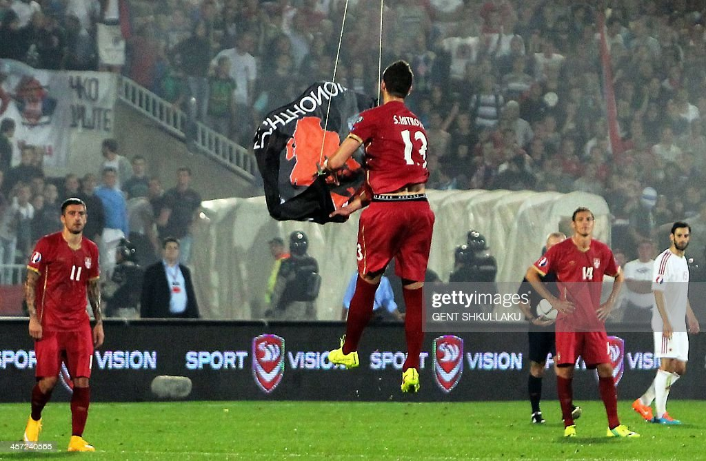 Serbia's defender Stefan Mitrovic grabs a flag with Albanian national symbols flown by a remotely operated drone during the UEFA Euro 2016 group I...