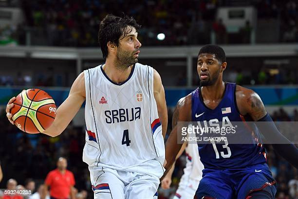 Serbia's guard Milos Teodosic holds on to the ball next to USA's guard Paul George during a Men's Gold medal basketball match between Serbia and USA...