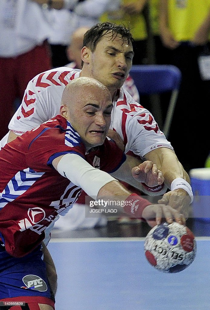 Serbia's Ivan Nikcevic (down) vies for the ball with Poland's Krzysztof Lijewski (up) during the handball pre-Olympic qualifying match Serbia vs Poland on April 7, 2012 at the Tecnificacion Center sports hall in Alicante. The match ended in a 25-25 draw.