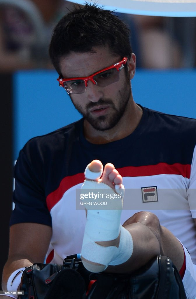 Serbia's Janko Tipsarevic looks at the strapping on his foot during a break in his men's singles match against Spain's Nicolas Almagro on the seventh day of the Australian Open tennis tournament in Melbourne on January 20, 2013.