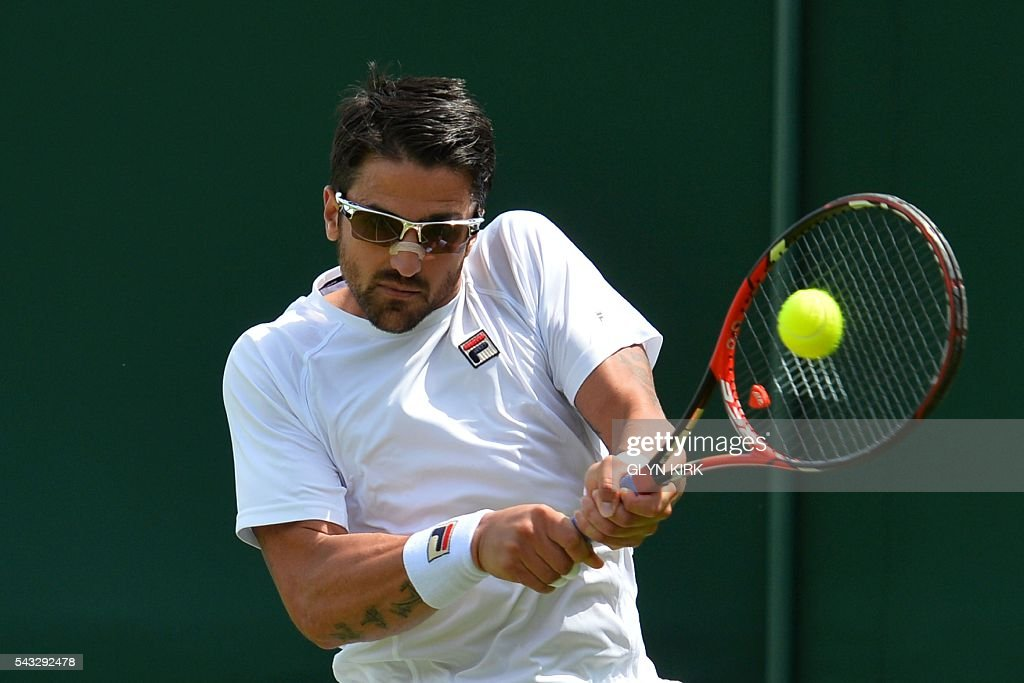 Serbia's Janko Tipsarevic returns against France's Gilles Simon during their men's singles first round match on the first day of the 2016 Wimbledon Championships at The All England Lawn Tennis Club in Wimbledon, southwest London, on June 27, 2016. / AFP / GLYN