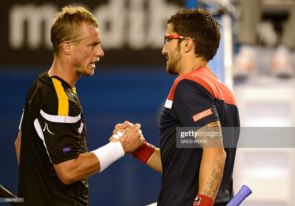 Serbia's Janko Tipsarevic (R) shakes hands after victory in his men's singles match against Australia's Lleyton Hewitt on first day of the Australian Open tennis tournament in Melbourne on January 14, 2013. AFP PHOTO/GREG WOOD IMAGE STRICTLY RESTRICTED TO EDITORIAL USE - STRICTLY NO COMMERCIAL USE