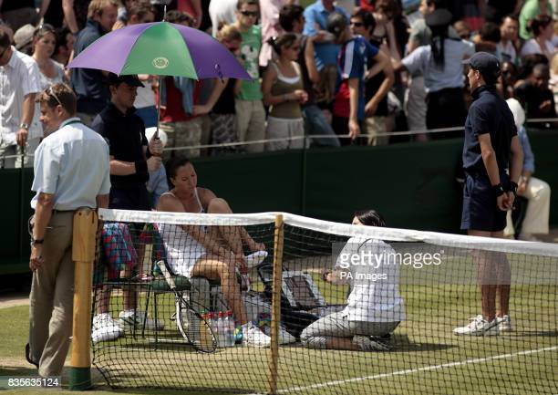 Serbia's Jelena Jankovic receives treatment from a physio during her match against USA's Melanie Oudin during the 2009 Wimbledon Championships at the...