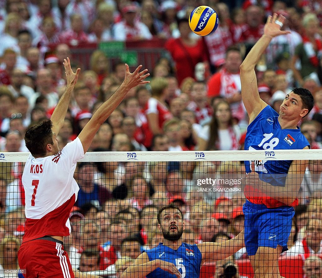 Serbia's Marko Podrascanin (R) spikes against Poland's Karol Klos during the opening match of the FIVB Mens Volleyball World Championship at the National Stadium in Warsaw on August 30, 2014. Poland won 25 - 19, 25 - 18 , 25 - 18. AFP PHOTO/JANEK SKARZYNSKI