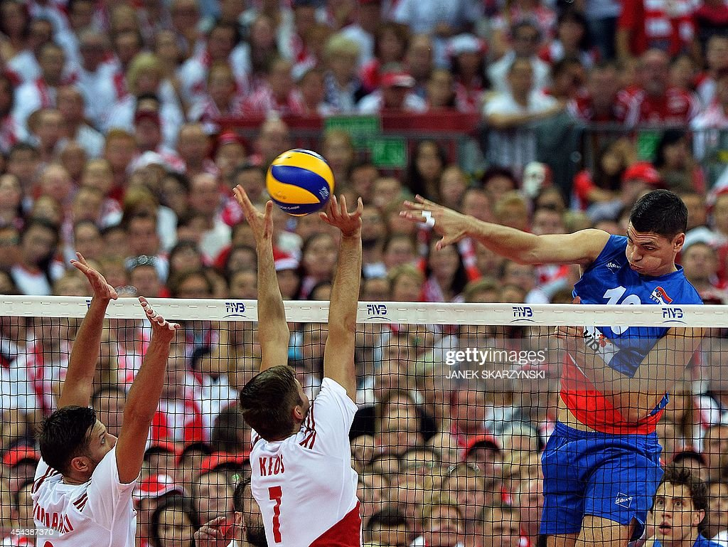 Serbia's Marko Podrascanin (R) spikes against Poland's Michal Winiarski (L) and Karol Klos during the opening match of the FIVB Mens Volleyball World Championship at the National Stadium in Warsaw on August 30, 2014. Poland won 25 - 19, 25 - 18 , 25 - 18.
