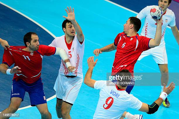 Serbia's Marko Vujin jumps to shoot as he faces with Croatia's Domagoj Duvnjak and Serbia's Alem Toskic during the men's preliminaries Group B...