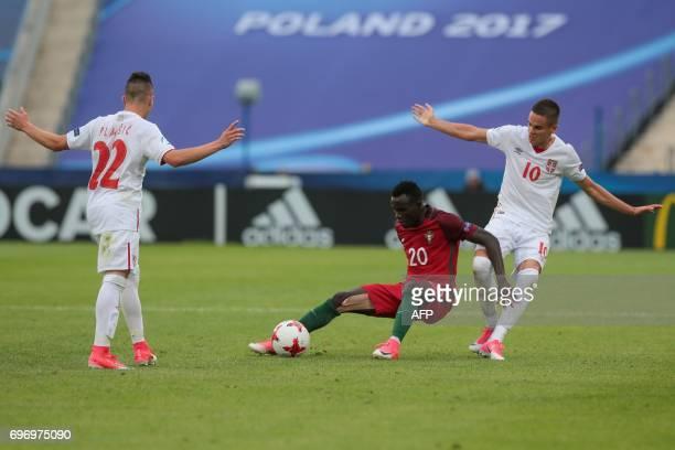 Serbia's midfielder Mijat Gacinovic and Serbia's midfielder Srdjan Plavsic vie with Portugal's midfielder Bruma during the UEFA U21 European...