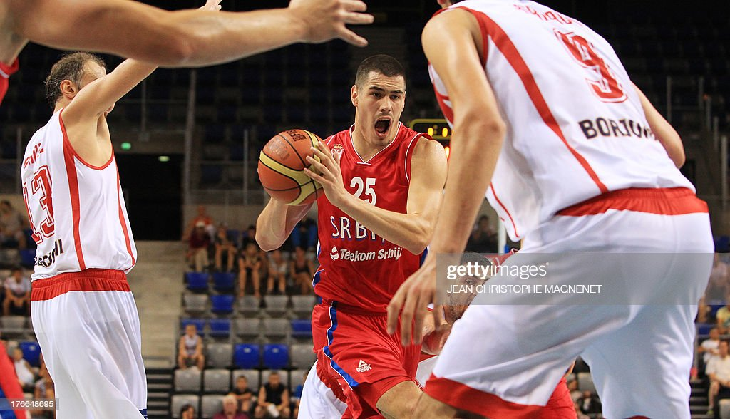 Serbia's national basketball team player Nikola Kalinic (C) vies with Georgia's national basketball players during the friendly basketball match between Serbia and Georgia, on August 16, 2013, in Antibes, southeastern France, as part of the preparation for the 2013 EuroBasket in Slovenia.