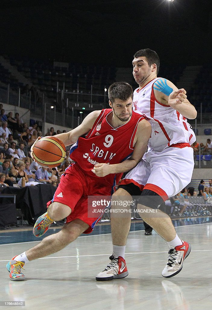 Serbia's national basketball team player Stefan Markovic (L) vies with Georgia's national basketball team player Beka Burjanadze during the friendly basketball match between Serbia and Georgia, on August 16, 2013, in Antibes, southeastern France, as part of the preparation for the 2013 EuroBasket in Slovenia.