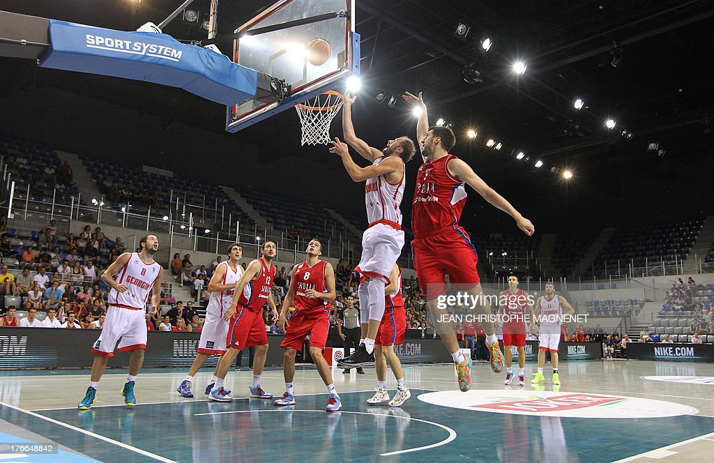 Serbia's national basketball team player Stefan Markovic (R) vies with Georgia's national basketball team player Viktor Sanikidze (C) during the friendly basketball match between Serbia and Georgia, on August 16, 2013, in Antibes, southeastern France, as part of the preparation for the 2013 EuroBasket in Slovenia.
