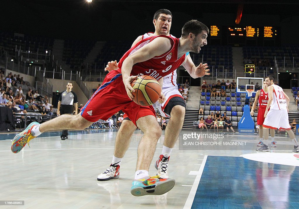 Serbia's national basketball team player Stefan Markovic (Front) vies with Georgia's national basketball team player Beka Burjanadze during the friendly basketball match between Serbia and Georgia, on August 16, 2013, in Antibes, southeastern France, as part of the preparation for the 2013 EuroBasket in Slovenia. AFP PHOTO / JEAN CHRISTOPHE MAGNENET