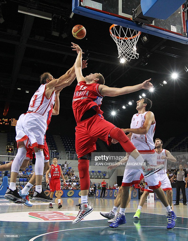 Serbia's national basketball team player Vladimir Stimac (C) vies with Georgia's national basketball team player Viktor Sanikidze (L) during the friendly basketball match between Serbia and Georgia, on August 16, 2013, in Antibes, southeastern France, as part of the preparation for the 2013 EuroBasket in Slovenia.