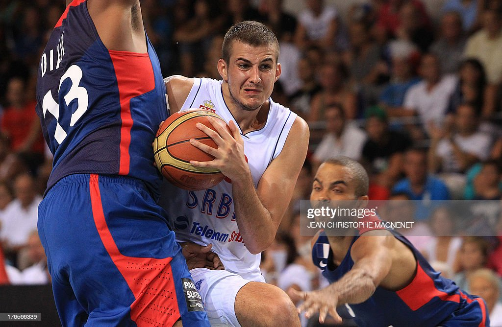 Serbia's Nemanja Bjelica (C) is challenged by France's Tony Parker (R) and Boris Diaw (L) during a friendly basketball match between France and Serbia on August 15, 2013 in Antibes, southeastern France as part of the preparation for the 2013 EuroBasket in Slovenia.