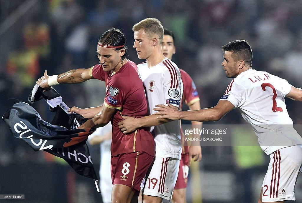 Serbia's Nemanja Gudelj scuffles with midfielder Albania's midfielder Bekim Balaj and defender Andi Lila over a flag with Albanian national symbols...