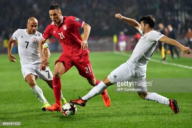 Serbia's Nemanja Matic vies with Georgia's Jaba Kankava and Davit Khocholava during the FIFA World Cup 2018 qualification football match between...