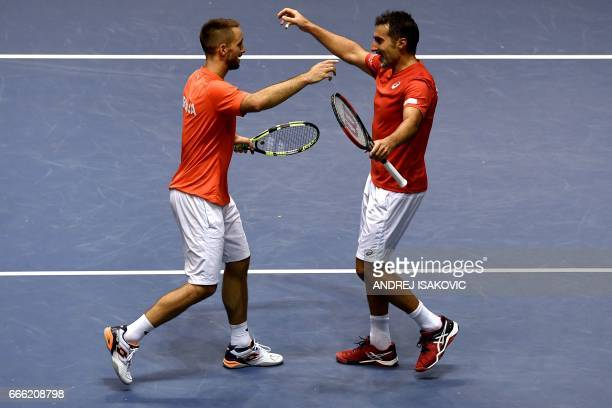 Serbia's Nenad Zimonjic and Viktor Troicki celebrate their victory after the Davis Cup quarterfinal tennis doubles match against Spain's Pablo...