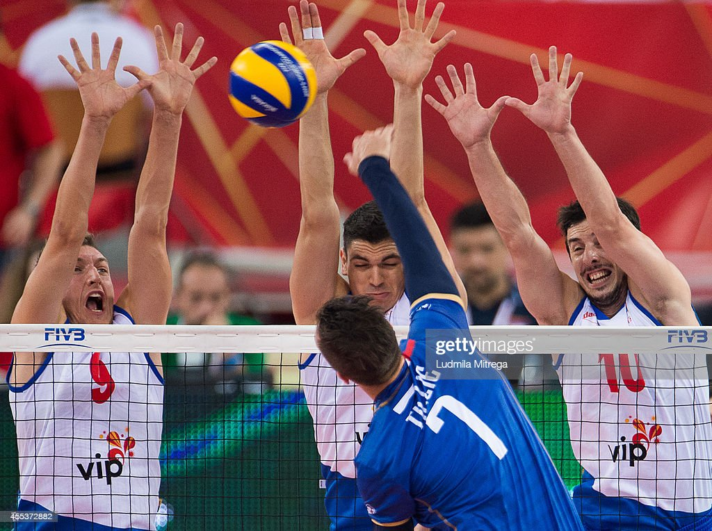 Serbia's Nikola Jovovic Marko Podrascanin and Milos Nikic block the ball during the FIVB World Championships match between Serbia and France on...