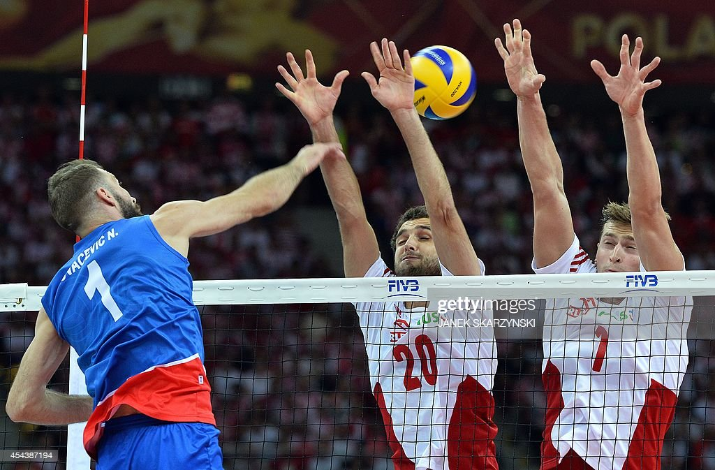Serbia's Nikola Kovacevic (L) spikes against Poland's Piotr Nowakowski (R) and Mateusz Mika during the opening match of the FIVB Mens Volleyball World Championship at the National Stadium in Warsaw on August 30, 2014. Poland won 25 - 19, 25 - 18 , 25 - 18.