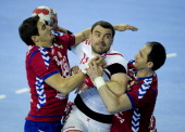 Serbia's Nikola Manojlovic and Alem Toskic vie with Poland's Bartosz Jurecki during the handball preOlympic qualifying match Serbia vs Poland on...