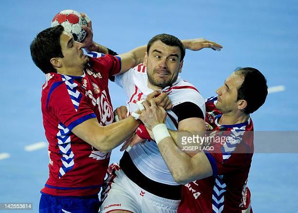 Serbia's Nikola Manojlovic and Alem Toskic vie with Poland's Bartosz Jurecki during the handball preOlympic qualifying match Serbia vs Poland on...