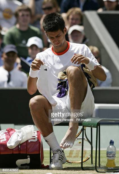 Serbia's Novak Djokovic after receiving treatment on his foot during his semifinal match against Spain's Rafael Nadal during The All England Lawn...
