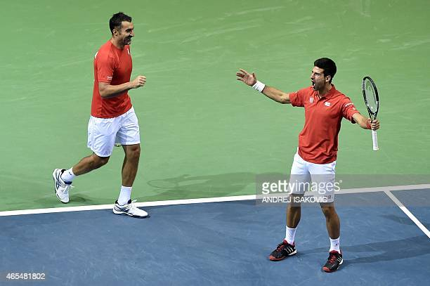 Serbia's Novak Djokovic and Nenad Zimonjic celebrate after gaining a point against Croatia's Marin Draganja and Franko Skugor during the Davis Cup...
