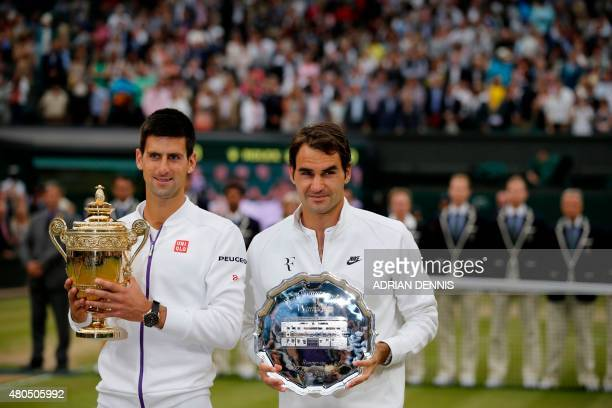 Serbia's Novak Djokovic and Switzerland's Roger Federer hold their trophies following the presentation after their men's singles final match on day...