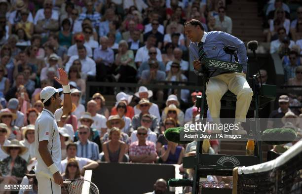 Serbia's Novak Djokovic argues with umpire Mohamed Lahyani during his match against Great Britain's Andy Murray on day thirteen of the Wimbledon...