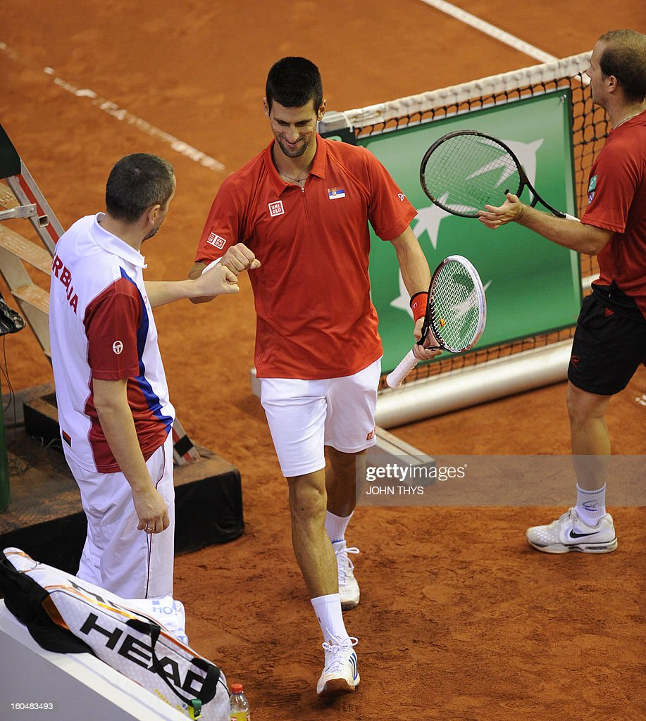 Serbia's Novak Djokovic (C) celebrates with Serbian's captain Bogdan Obradovic (L) and Belgium's Olivier Rochus (R) during their Davis Cup World Group first round tennis match on February 1, 2013 in Charleroi. AFP PHOTO /JOHN THYS